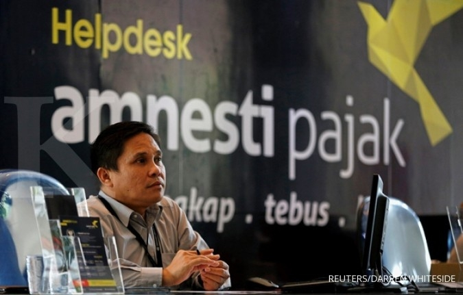 An officer assists a tax amnesty participant at the country's tax headquarters in Jakarta